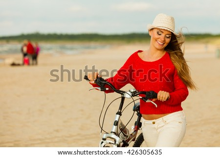 Sports and recreation. Attractive smiling woman with bicycle walks on beach near to sea. Young long haired gorgeous tourist spends time on seaside. - stock photo