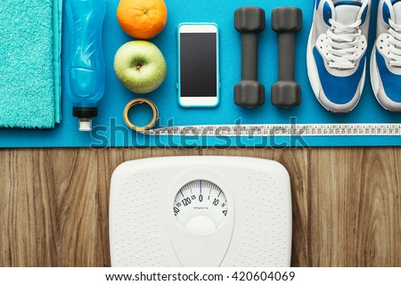 Sports and workout equipment on a wooden floor with healthy snacks, weight loss and physical activity concept - stock photo