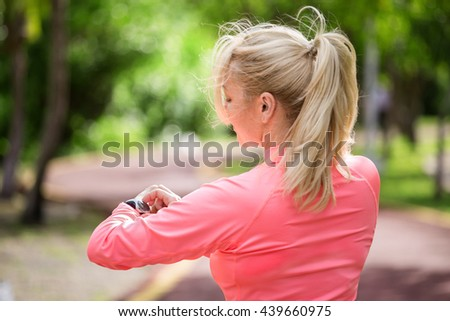Sports athlete runner woman looking at heart rate monitor after jogging. Healthy lifestyle and sport concept  - stock photo