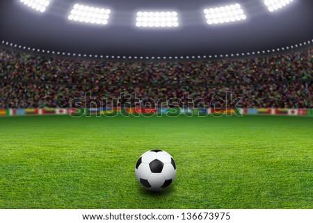 Sports background - soccer ball on green stadium, arena in night illuminated bright spotlights - stock photo