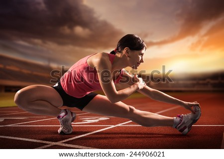 Sports background. Young sportswoman stretching and preparing to run. - stock photo