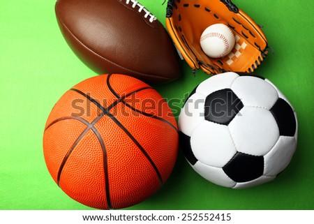 Sports balls on green background - stock photo