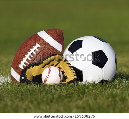 Sports balls on the field with yard line. Soccer ball, American football and Baseball in yellow glove on green grass. Outdoors   - stock photo