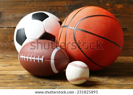 Sports balls on wooden background - stock photo