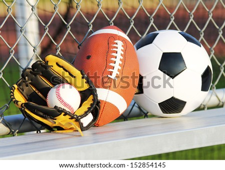 Sports balls. Soccer ball, american football and baseball in yellow glove. Outdoors - stock photo