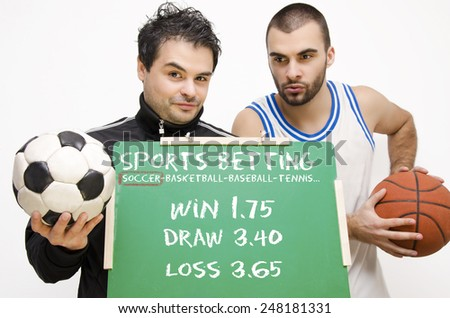 Sports Bets, bookies, football player holding blackboard with betting odds,basketball player in background. Selective focus on guy in foreground - stock photo