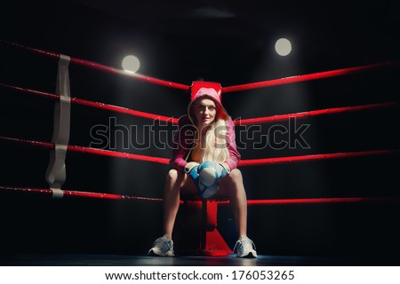 Sports Boxing Woman in box gloves sitting on ring - stock photo