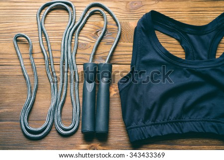 Sports bra and jump rope on wooden background. The view from the top. - stock photo