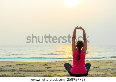 sports by the ocean. woman doing yoga - stock photo
