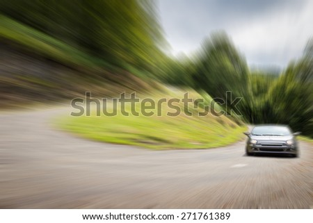 Sports car racing a winding road with sharp curve up the mountain - stock photo