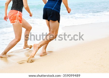 Sports. Closeup Of Athletic Runners Legs Running On Beach. Sporty Fit Couple Jogging On Sand Near Sea During Outdoor Workout. Fitness And Exercising. Healthy Lifestyle And Wellness. Health Concept