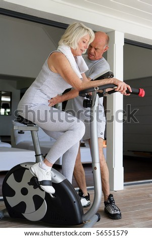 Sports Coach caring for an elderly woman sitting on a bike - stock photo