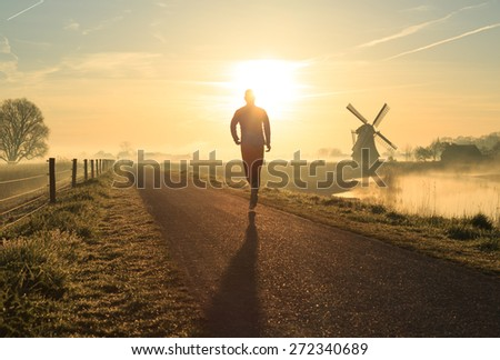 Sports concept: athlete running in the foggy, Dutch countryside near a windmill during sunrise. - stock photo