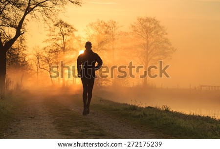 Sports concept: silhouette of a man running during a foggy, spring sunrise in the countryside. - stock photo