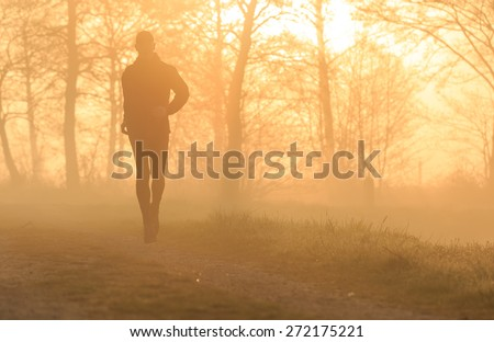 Sports concept: silhouette of a man running during a foggy sunrise in the countryside. - stock photo