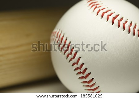 Sports concept with a close up of a new baseball and wooden bat