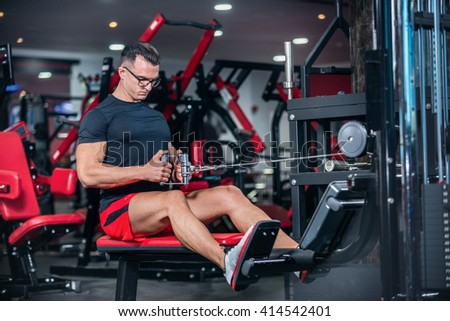 Sports day begins with a warm-up. Strong athlete doing exercise at the gym. The athlete does a workout at the sports simulator. - stock photo