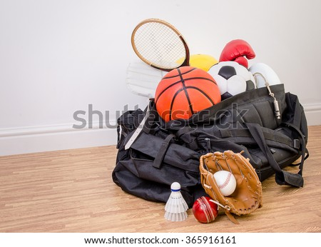 sports equipment in a holdall sports bag on a gym floor. football, rugby, baseball, cricket, basketball, boxing, badminton, squash. with copy space. - stock photo