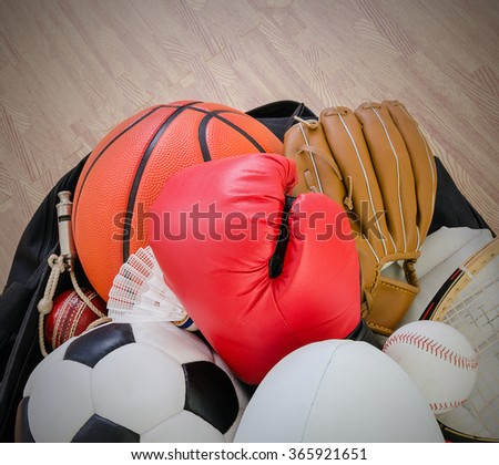 sports equipment in a holdall sports bag on a gym floor. football, rugby, baseball, cricket, basketball, boxing, badminton, squash. - stock photo