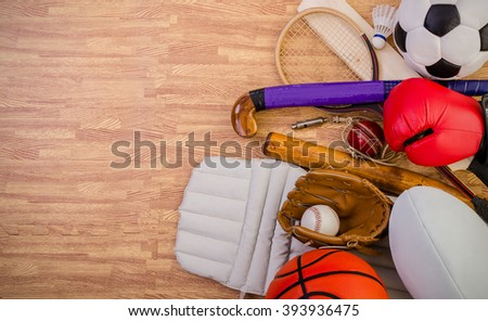 sports equipment on a gym floor, football, hockey stick, rugby ball, baseball, cricket bat and pads, basketball, boxing gloves, badminton and squash racket.