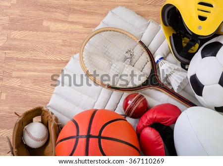 sports equipment on a gym floor, football, rugby, baseball, cricket, basketball, boxing, badminton and squash.  - stock photo