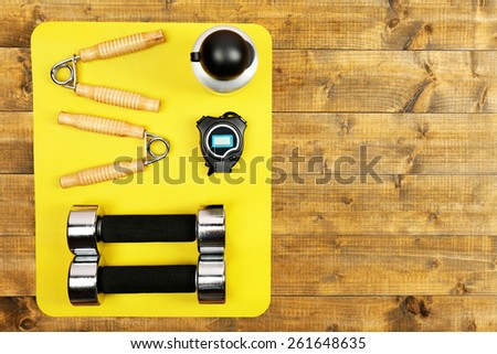 Sports equipment on mat on wooden floor, top view - stock photo