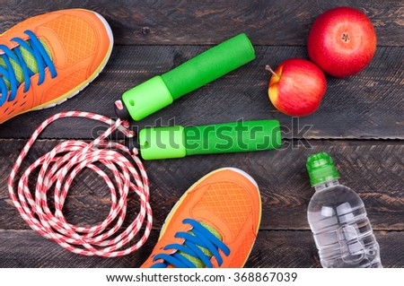 Sports equipment. Sport shoes, skipping rope, apple and bottle of water on the old dark wooden background. Sport and healthy life concept. Top view - stock photo