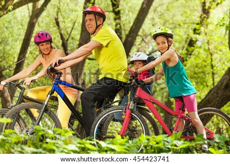 Sports family having fun cycling in the forest