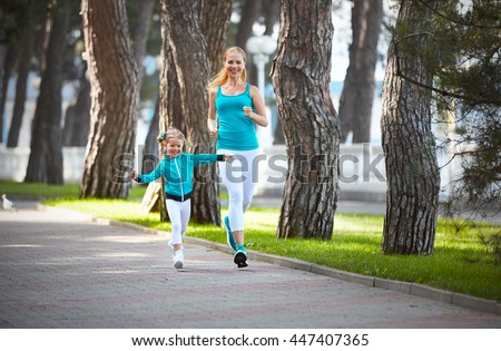sports family mother and child daughter are engaged in running and athletics in the summer in the park