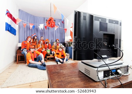 Sports fans watching a game of their national team on the television at home in a living room, full of anticipation - stock photo