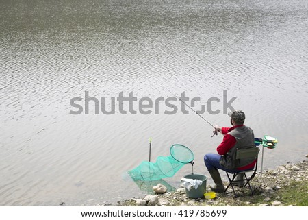 Sports Fisherman With Fishing Equipment, Sitting On The Lake Coast And Fishing, Small Waves On The Water Surface - stock photo