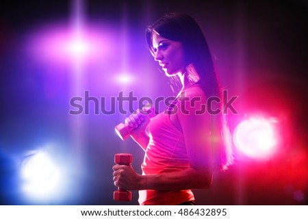 Sports fitness girl with slim stomach works dumbbells in multi-colored rays of fitness room. Beautiful sport girl with long hair keeps dumbbells.