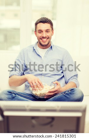 sports, food, happiness and people concept - smiling man with popcorn watching sports on tv and supporting team at home - stock photo