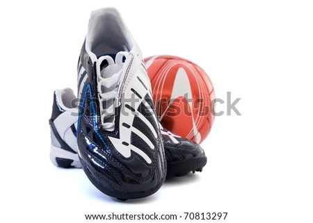 Sports footwear and red soccer ball on a white background - stock photo