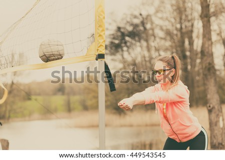 Sports games and people concept. Young woman in sportswear volleyball player in action outdoor on court