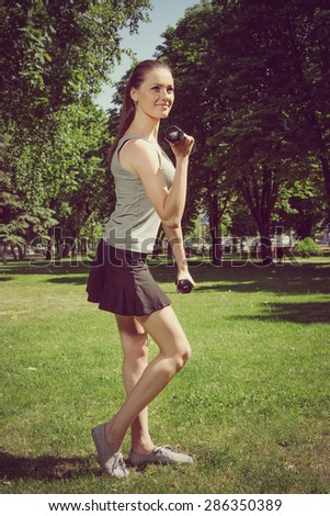 Sports girl doing exercise with easy dumbbells standing sideways on the green grass outdoors. Healthy lifestyle concept. - stock photo
