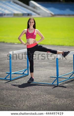 Sports girl doing stretching engaged athletics stadium - stock photo