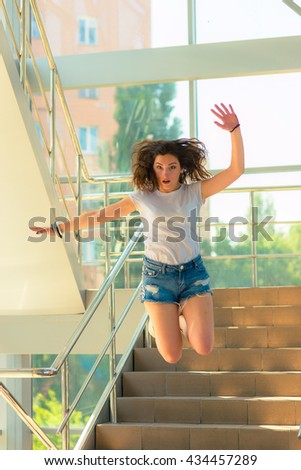 sports girl in a vest and denim shorts on the stairs