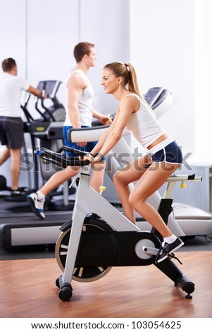 Sports girl on bikes in the gym - stock photo
