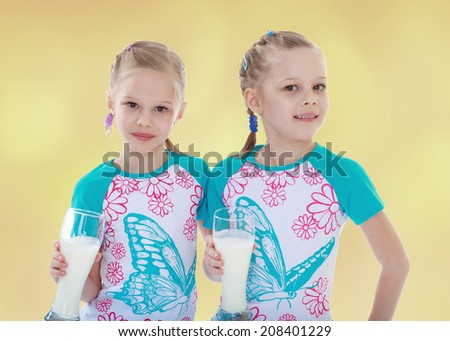 Sports girl twins with a glass of milk.kindergarten, the concept of childhood and joy, teens - stock photo