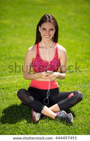 Sports girl with headphones sitting on the grass listening to music