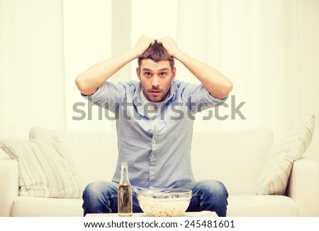 sports, happiness and people concept - sad man watching sports on tv and supporting team at home - stock photo