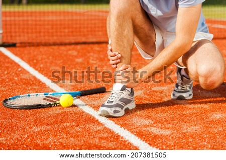 Sports injury. Close-up of tennis player touching his leg while sitting on the tennis court - stock photo
