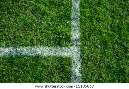 Sports lines painted on a green grassy playing field. - stock photo