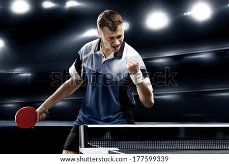sports man celebrates victory on the dark background with lights - stock photo
