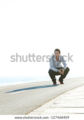 Sports man crouching down on running track by the sea, with a blue sky in the background, on a sunny day. - stock photo