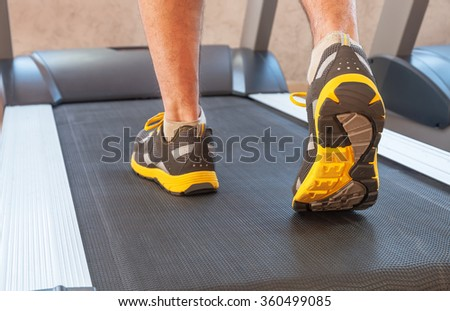 sports man in a gym on treadmill in sport shoes - stock photo