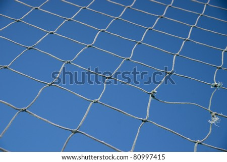 Sports net with rime frost on blue sky