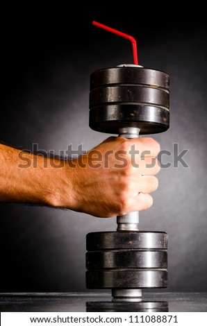 sports nutrition. male hand is holding metal barbell with red straw - stock photo