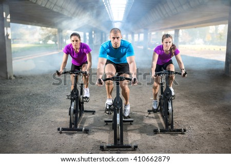 sports people training bike riding on exercise bicycle